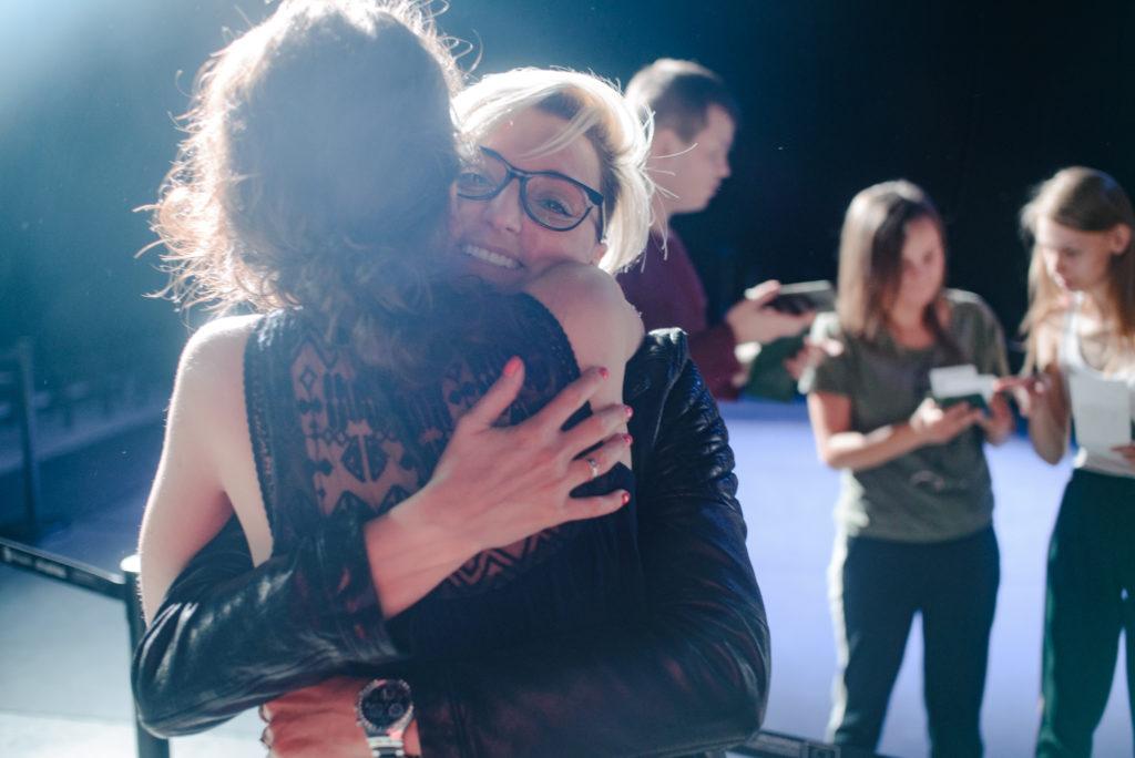 Na pierwszym planie dwie przytulające się kobiety. W tle uczestnicy spektaklu.